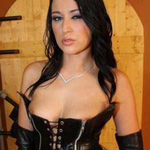 Brunette bossy type Ashley strutting about dungeon space partly naked in fetish outfit