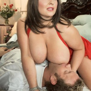 Dark-haired MILF Angel Gee unsheathing huge hooters from transparent sundress for nip sucking