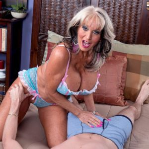 Magnificent over 50 MILF Sally D'Angelo showcasing enormous fun bags while seducing stud for sex on bed
