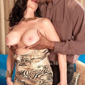 Mature brunette pornstar Rita Daniels exposing big tits before interracial sex