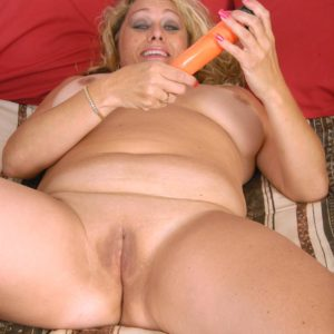 Thick mature blonde woman doffing lingerie and panties before masturbating