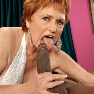 Crimson hair grandma pornstar Valerie sucking off a enormous ebony prick in white lingerie