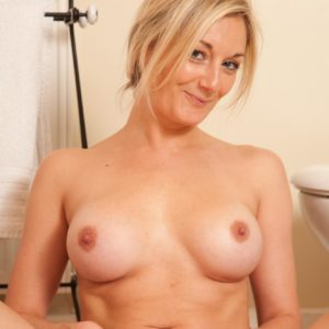 Elder golden-haired solo model undressing nude to pose nude in the bathroom