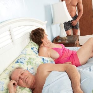 Busty redhead grandma Bea Cummins jerking off enormous rod while cuck spouse sleeps