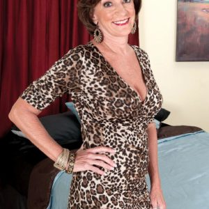 Solo grannie Sydni Lane taunting on bed by displaying boulder-holder in nylons
