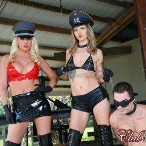 Two dominas in hats and long boots lead masculine submissive by a leash