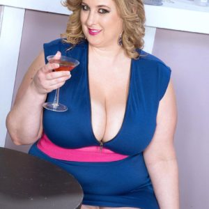 Blond big sexy lady Amiee Roberts reveals her immense juggs from her dress over a glass of champagne
