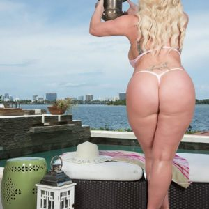 Light-haired BIG HOT LADY Holly Sausage struts about in a thong bathing suit next to the ocean