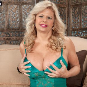 Mature yellow-haired dame Miss Deb looses her big boobies from her lingerie on a sofa