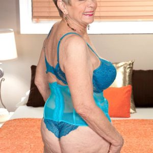 Short haired 60 plus MILF Lin Boyde unveiling humungous tits from lingerie in stockings