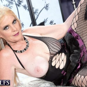 Over sixty blond MILF unveiling gigantic natural boobs in ripped stockings and lengthy boots