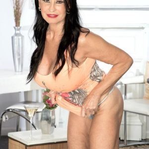 Over sixty dark haired MILF Rita Daniels displaying amazing pins and huge boobs