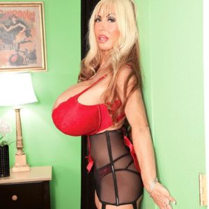 Platinum-blonde solo model Elizabeth Starr shows her monster fun bags in a red brassiere