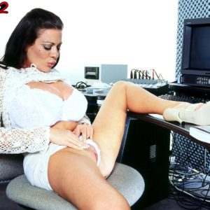 Black-haired MILF Linsey Dawn McKenzie unsheathes her giant tits at her office place desk