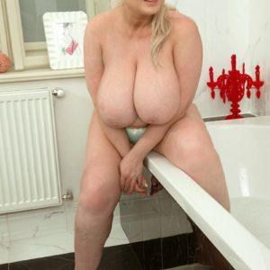 Blond BIG HOT WOMAN Samantha Sanders looses her gigantic titties as she readies for a bathtub
