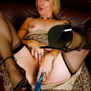 Mature golden-haired broad hikes up her dress in order to toy her cunt in black stockings