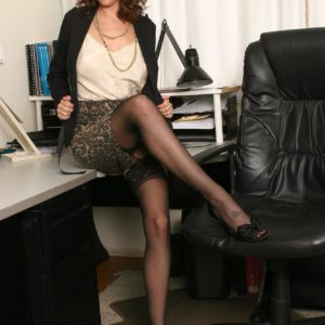 Beautiful elderly woman strips to her black hosiery only in her home office
