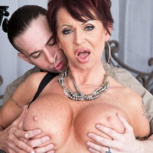 Fashionable aged dame Gina Milano tempts a younger man with her huge melons