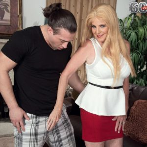 Mature golden-haired doll Charlie has her hefty hooters uncovered by junior guy in a red micro-skirt