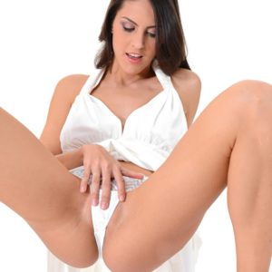 Solo female Carolina Abril strips off her milky dress and bloomers before fingering her honeypot