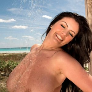Dark-haired MILF Arianna Sinn flaunts her gigantic breasts in the outdoors with the ocean in view