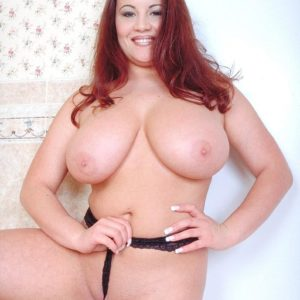 Redhead MILF Annie Swanson wets her huge boobies in the bathtub during solo action