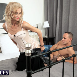 Provocative blonde grannie Beata entices a junior dude in a black microskirt and hosiery