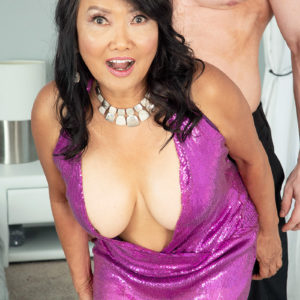 Sixty Plus Oriental MILF Mandy Thai wears no brassiere under her dress while seducing a man