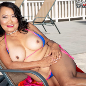 60 Plus Asian MILF Mandy Thai strips off a rope bathing suit to get au naturel by a pool