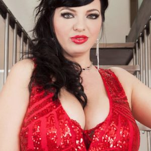 Dark haired model Joana Bliss sets her superb breasts free of a short crimson sundress in crimson heels