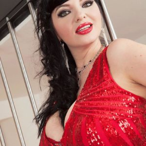 Dark haired model Joana Bliss sets her superb breasts free of a short crimson sundress in crimson heels