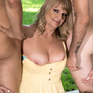 Plumper Sixty plus blond Mia Magnusson seduces the gardeners outdoors for MMF sex