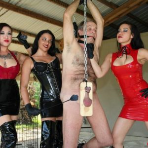 Cruel females with dark hair torture a masculine submissive fully clothed in latex and lengthy boots