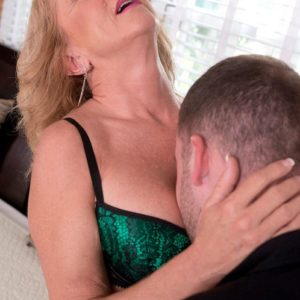 Foxy ash-blonde cougar Cali Houston is freed from enticing lingerie on a bed by her toy man