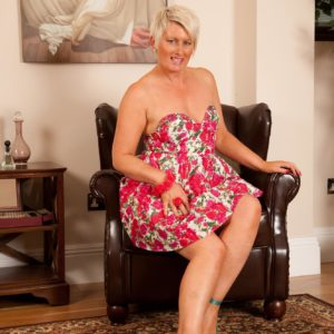 Mature platinum ash-blonde lets out her tiny boobies as she strips to high-heeled shoes on a leather tabouret