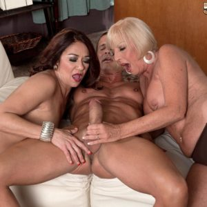 Aged chicks Renee Ebony and Scarlet Andrews take turns sucking a rock-hard cock