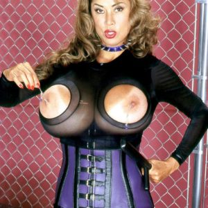 Babe Minka demonstrates off her huge tits in a cupless onesie and a waist cincher