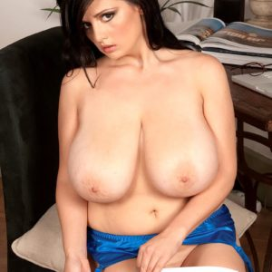 Brown-haired MILF Arianna Sinn sets her monster-sized boobs free in see thru hosiery and stilettos