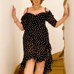 Mature red-haired doffs a dress and pretties to pose totally naked on wooden stairs