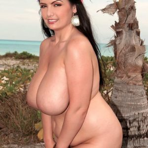Thick female Arianna Sinn uncups her melons as she gets nude by a tropical tree