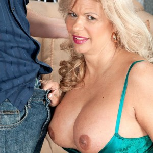 Accomplished golden-haired broad Miss Deb bares her huge tits from her lingerie on a futon