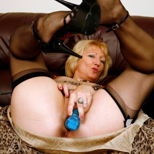 Aged yellow-haired dame hikes up her dress in order to toy her twat in black nylons