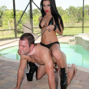 Alluring dark haired Adriana Lynn makes a collared male submit to her will in stiletto boots