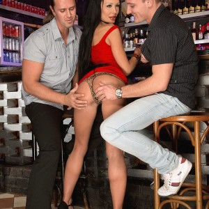Alluring MILF Patty Michova gives two guys blow job simultaneously in a bar