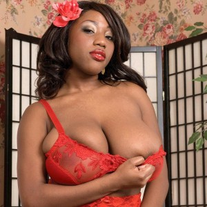 Black MILF Janet Jade revealing gigantic boobies while outfitted nylons and garters