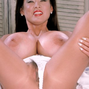 Chinese solo model Minka exposes her bush with her huge boobs on exhibit on a bed