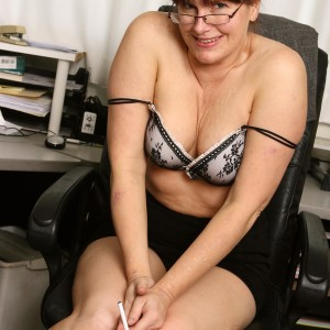 Elderly secretary makes her nude modeling debut while at work during solo action