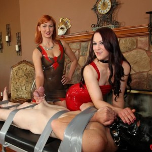 Fully-clothed females Cheyenne and Amadahy tug on a held man's dick in latex wear