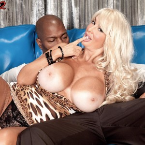 Long legged blonde MILF Brittany O'Neil unveiling huge boobies for black guy on leather couch