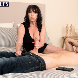 Sixty plus MILF Christina Starr entices a young guy while going bare-chested in a black dress